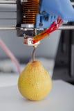 Uma pera suculenta madura funcionamento da impressora 3d do dispositivo durante os processos Imagem de Stock Royalty Free