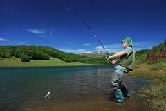 Uma pesca do pescador em um lago Mavrovo fotografia de stock royalty free