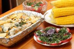 Uma pescada posta de conserva com batatas e especiarias cozeu no forno, na placa com saladas e no milho Imagens de Stock Royalty Free