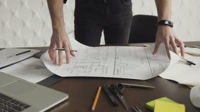 Uma pessoa é um arquiteto ou um coordenador que estejam trabalhando em um projeto dos bens imobiliários no local de trabalho vídeos de arquivo