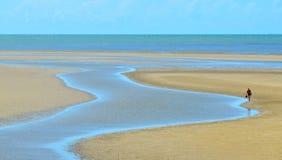 Uma pessoa anda ao longo de um córrego em uma praia selvagem no Au de Queensland Fotografia de Stock Royalty Free