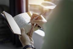 Uma pessoa bem sucedida nova que toma notas em um jornal pessoal imagem de stock royalty free