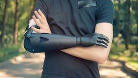 Uma pessoa com uma prótese da mão cruza os braços, fim acima
