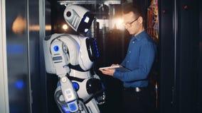 Uma pessoa controla um robô em um centro de dados, fecha-se acima
