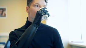 Uma pessoa deficiente bebe, usando seu braço artificial 4K filme
