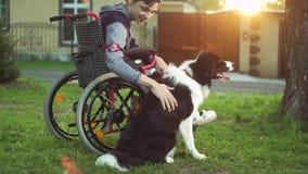 Uma pessoa deficiente joga com um cão, terapia do canitis, tratamento da inabilidade com o treinamento com um cão, homem na video estoque
