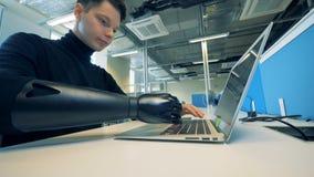 Uma pessoa deficiente trabalha no escritório, datilografando em um portátil 4K filme