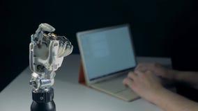 Uma pessoa está datilografando em um portátil e um braço cybernetic está movendo-se vídeos de arquivo