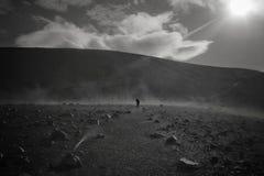 Uma pessoa no preto que fica no campo com as rochas na distância fotos de stock