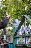Uma pessoa pinta a porta com pintura para proteger o produto da corros?o imagens de stock royalty free
