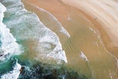 Uma pessoa que anda ao longo de uma praia abandonada Imagens de Stock