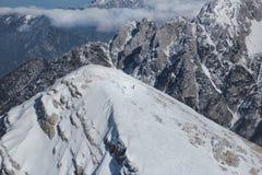 Uma pessoa que esquia para baixo com sol e montanhas fotos de stock