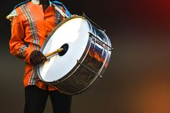 Uma pessoa que joga a pele de tambor, - a pele de tambor é um instrumento musical que seja soado sendo golpeado ou ser raspada po fotografia de stock