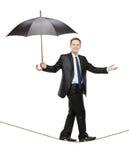 Uma pessoa que prende um guarda-chuva e que anda em uma corda Imagens de Stock Royalty Free