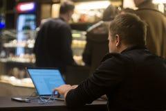 Uma pessoa que surfa a Web em um lugar público, fora de foco Imagem de Stock Royalty Free