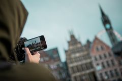 Uma pessoa que toma uma foto com um telefone de construções europeias imagem de stock royalty free