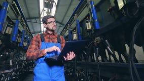 Uma pessoa trabalha com máquinas em uma sala de ordenha, usando o portátil vídeos de arquivo