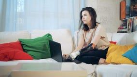 Uma pessoa trabalha com um portátil, prótese biônico vestindo, fim acima