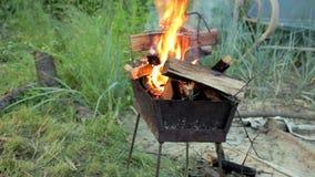Uma pilha ardente da madeira na grade na jarda filme