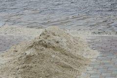 Uma pilha da areia cinzenta no passeio na costa do lago foto de stock royalty free