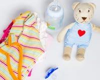 Uma pilha da roupa das crianças, brinquedos, chupeta em um backgr branco Fotografia de Stock