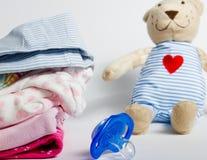 Uma pilha da roupa das crianças, brinquedos, chupeta em um backgr branco Imagens de Stock