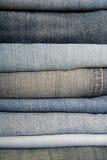 Uma pilha das calças de brim Fotos de Stock