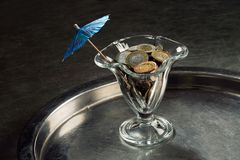 Uma pilha das moedas em um vidro de cocktail Fotografia de Stock