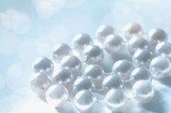 Uma pilha das pérolas em um fundo azul e branco imagem de stock