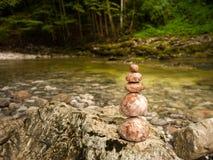 Uma pilha das pedras ao lado de um rio nos cumes austríacos foto de stock royalty free