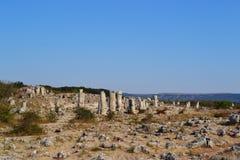 Uma pilha das pedras dispersou no céu azul brilhante da areia em um quente foto de stock