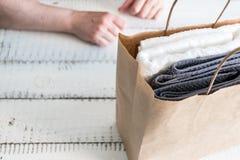 Uma pilha das toalhas de banho brancas colocadas em um pacote de papel no fundo branco Termas e bem-estar, matéria têxtil de terr Fotografia de Stock Royalty Free
