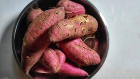 Uma pilha de batatas doces no fundo branco fotografia de stock royalty free