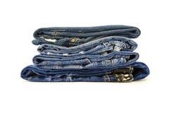 Uma pilha de calças da sarja de Nimes em um fundo branco Foto de Stock Royalty Free