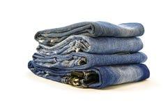 Uma pilha de calças da sarja de Nimes em um fundo branco Imagens de Stock Royalty Free