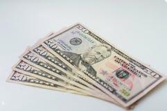 Uma pilha de cinqüênta notas de dólar ventilou para fora em um fundo branco Fotografia de Stock