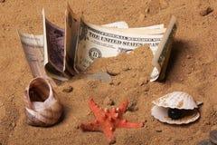 Uma pilha de dinheiro que encontra-se na areia com shell imagens de stock