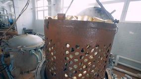 Uma pilha de latas de lata em um recipiente oxidado está sendo elevado de uma caldeira filme
