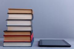 Uma pilha de livros e de uma tabuleta em seguida O conceito da educação foreground foto de stock royalty free