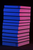 Uma pilha de livros na luz cor-de-rosa e azul Foto de Stock
