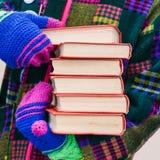 Uma pilha de livros nas mãos de um homem na roupa brilhante Um homem distribui livros na rua Promoção do livro Seis livros com a imagens de stock royalty free