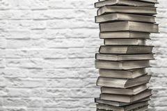 Uma pilha de livros velhos no fundo da parede de tijolo Imagens de Stock Royalty Free
