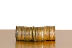 Uma pilha de moedas, colocada horizontalmente em um fundo branco fotos de stock royalty free