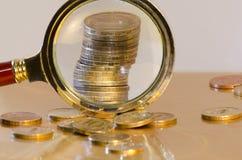 Uma pilha de moedas sob uma lupa fotografia de stock royalty free