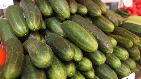 Uma pilha de pepinos frescos orgânicos no mercado filme