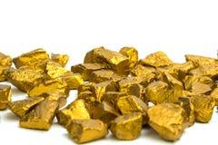 Uma pilha de pepitas de ouro ou de minério do ouro no fundo branco, pedra preciosa ou protuberância do conceito dourado da pedra, imagens de stock