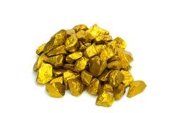 Uma pilha de pepitas de ouro ou de minério do ouro no fundo branco, pedra preciosa ou protuberância do conceito dourado da pedra, fotografia de stock