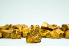 Uma pilha de pepitas de ouro ou de minério do ouro no fundo branco, pedra preciosa ou protuberância do conceito dourado da pedra, fotos de stock