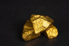 Uma pilha de pepitas de ouro ou de minério do ouro no fundo preto, pedra preciosa ou protuberância do conceito dourado da pedra,  fotografia de stock