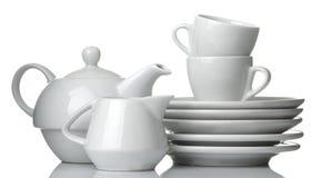 Uma pilha de pratos dinnerware placas, chaleira e copo em um fundo isolado branco Close-up fotografia de stock royalty free